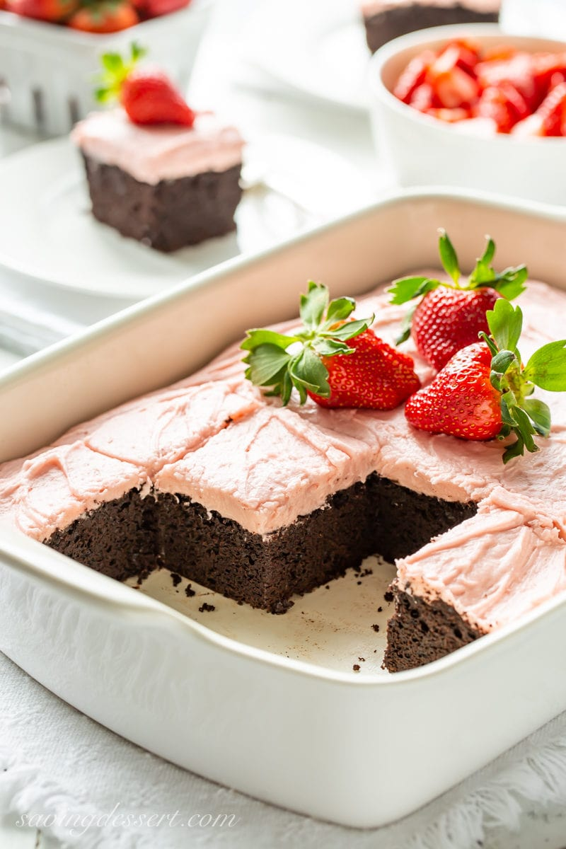 A sliced dark chocolate sheet cake with strawberry frosting and fresh strawberry garnish