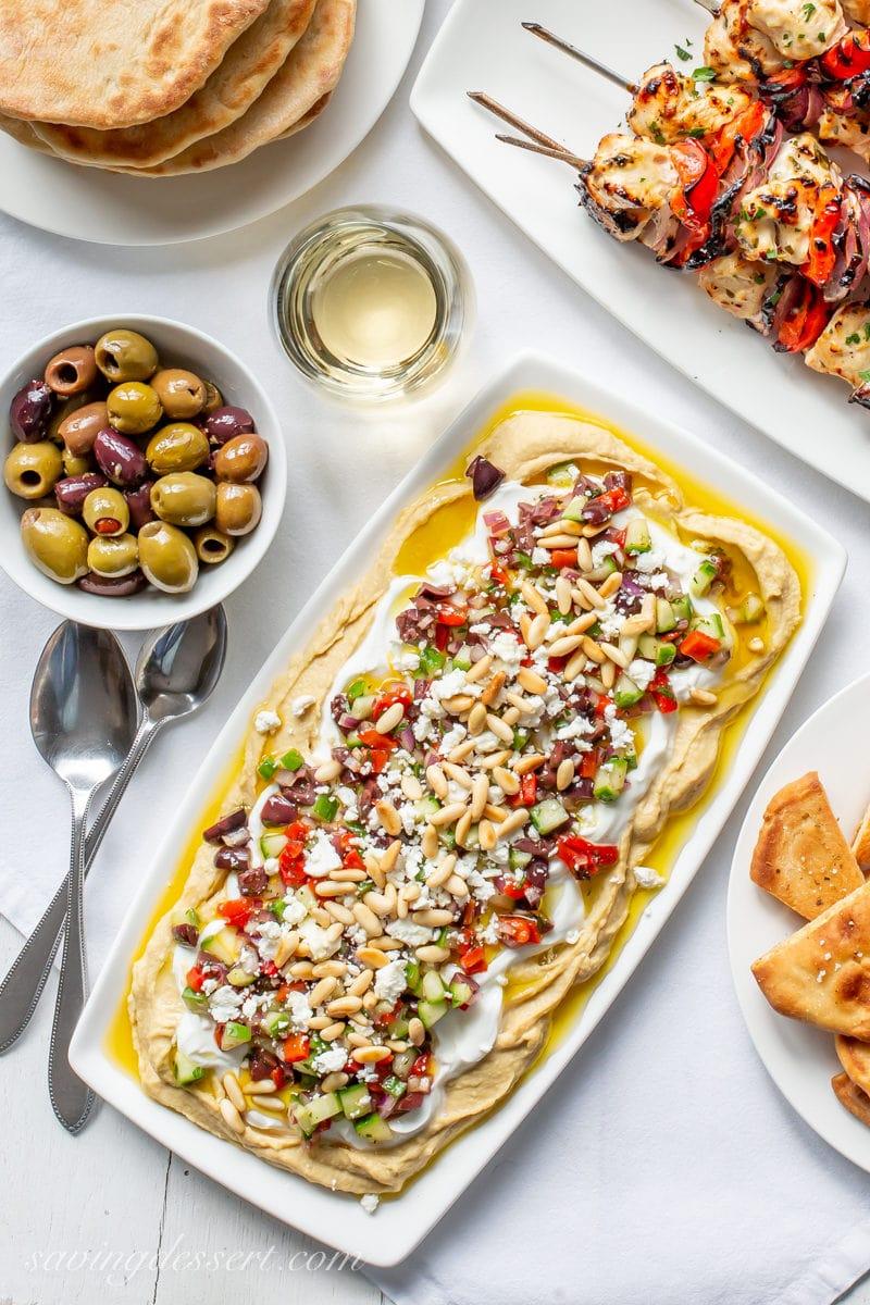 A platter of Greek Hummus Dip, olives, fresh pita bread and Greek marinated chicken kabobs
