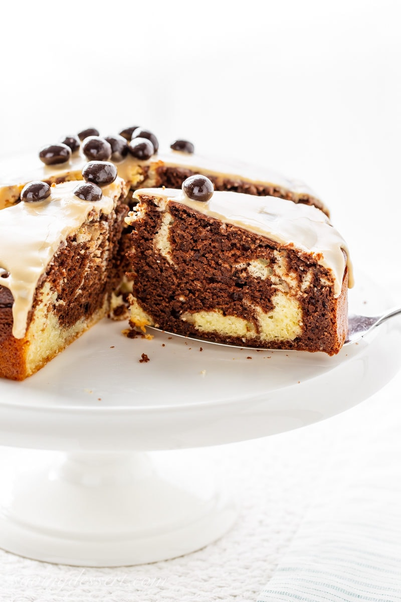 A sliced, marbled Irish Cream Breakfast Cake with a coffee glaze and espresso beans