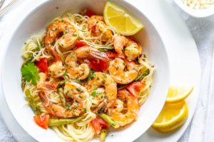 A bowl of shrimp scampi with tomatoes and asparagus over angel hair pasta