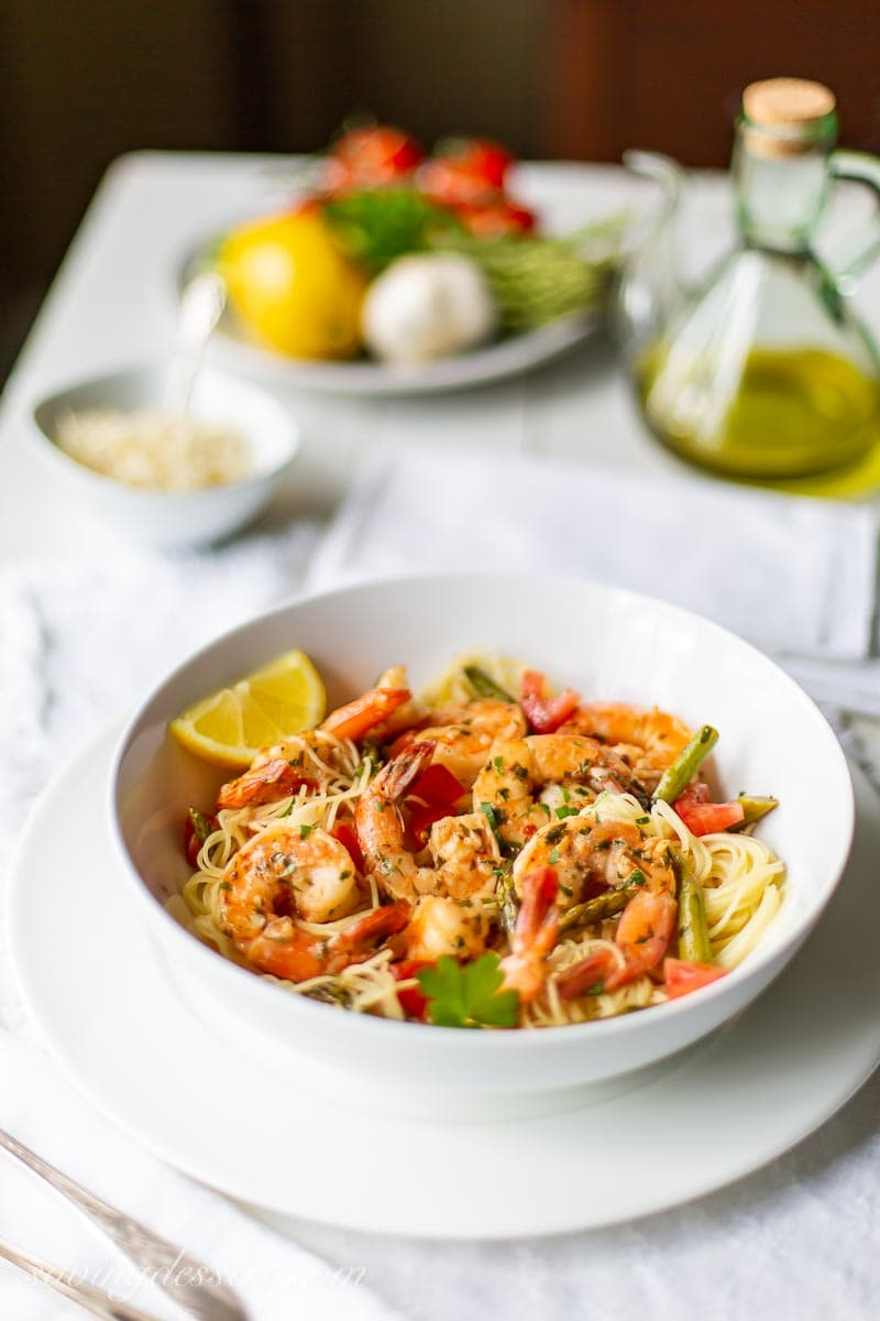 A table with a bowl of shrimp and pasta, olive oil and fresh vegetables