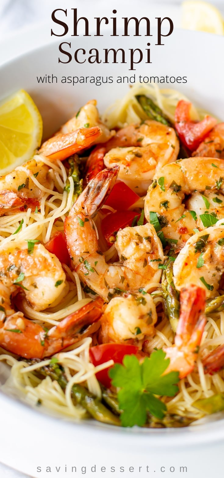 A bowl of angel hair pasta topped with garlic shrimp, tomatoes and asparagus