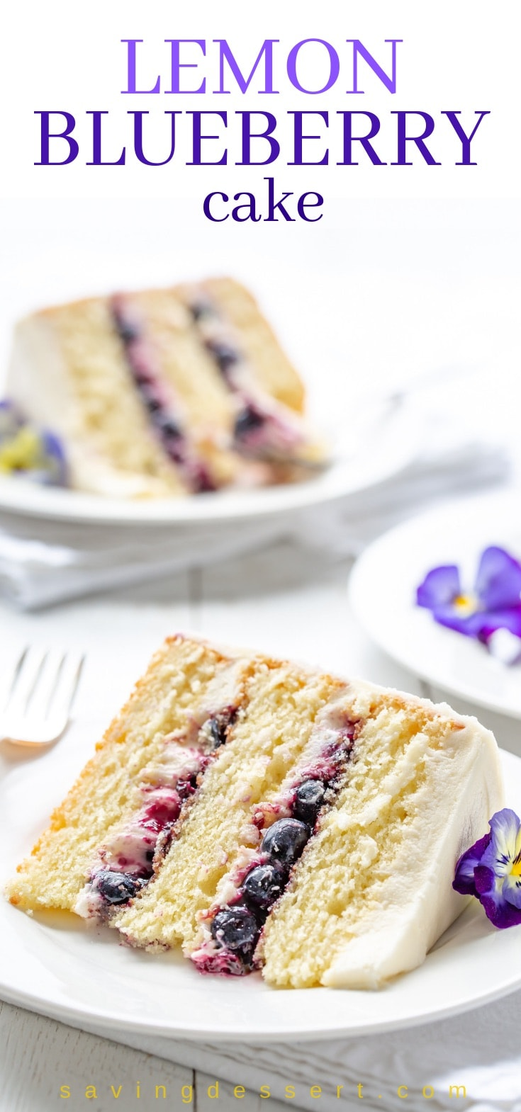 A big slice of Lemon Blueberry Cake decorated with purple pansies