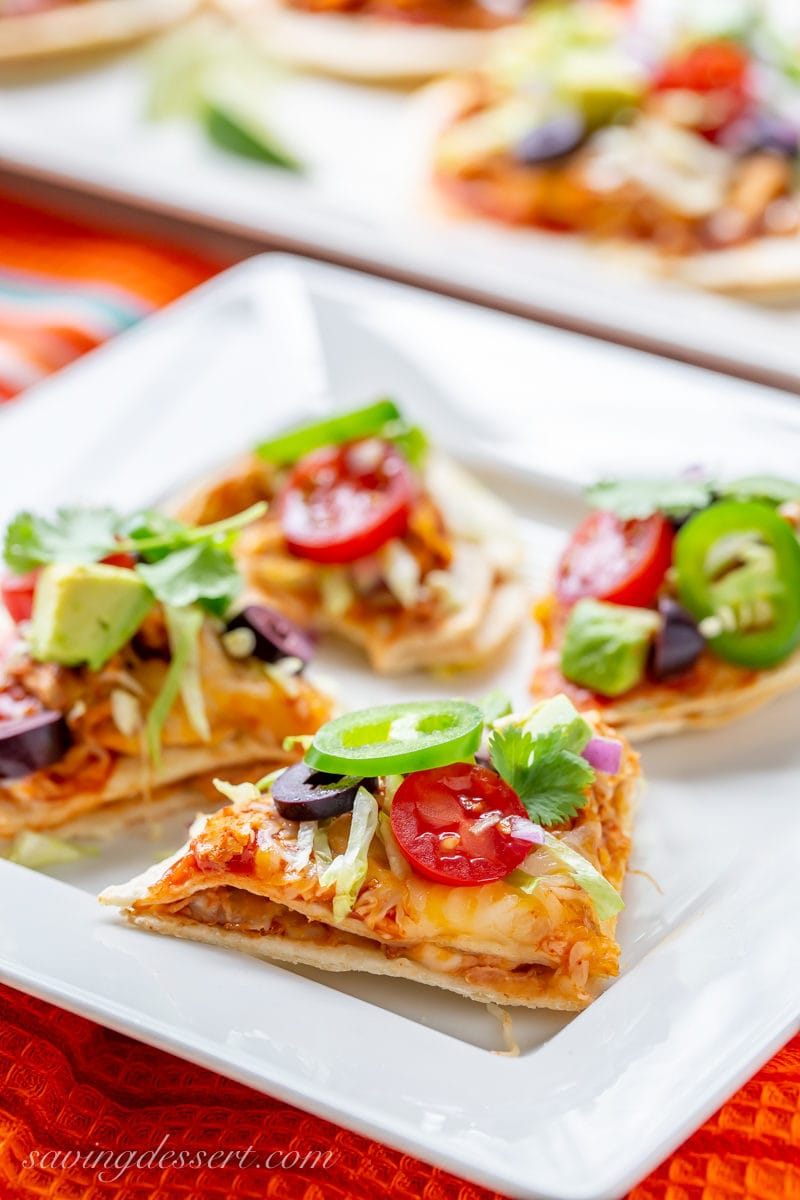 Nacho style Mexican Taco Pizzas with jalapeños, tomato, olives, lettuce and cilantro