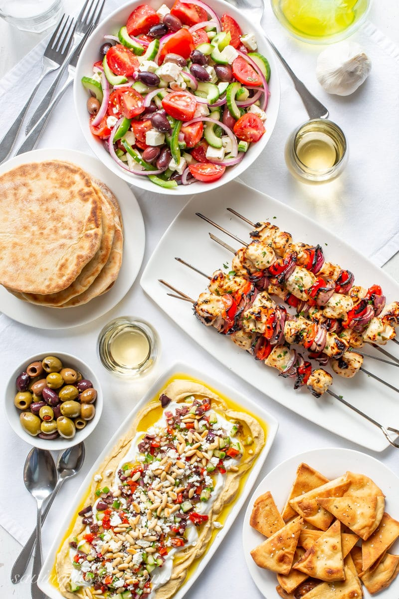 A Greek themed dinner party with whole wheat pita breads, pita chips, olives, wine, Greek salad, chicken kabobs and a layered Greek hummus dip