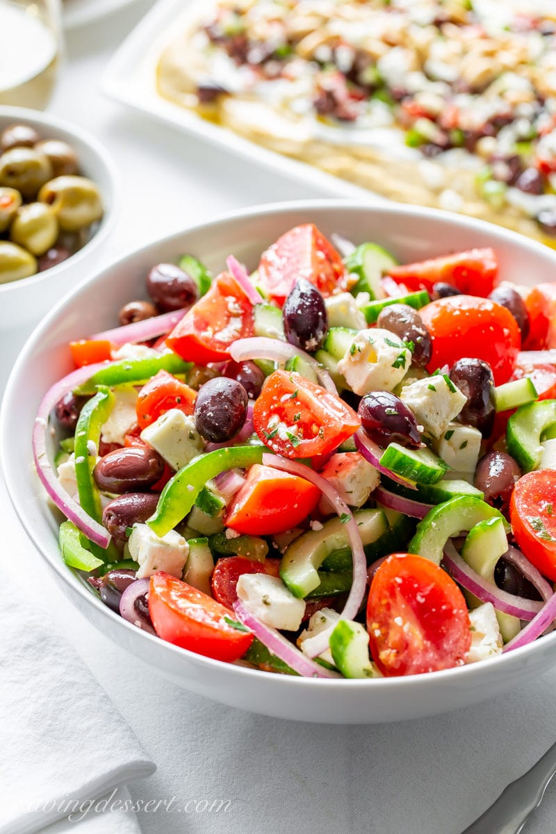 A bowl of fresh Greek Salad with olives, onions, feta cheese, cucumbers and tomatoes.
