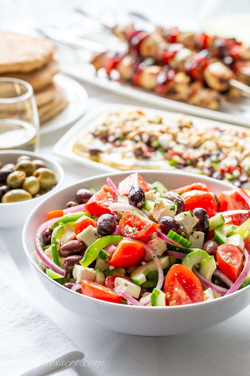 A table set with a big bowl of Greek Salad, olives, pita bread, layered Greek dip and chicken kabobs
