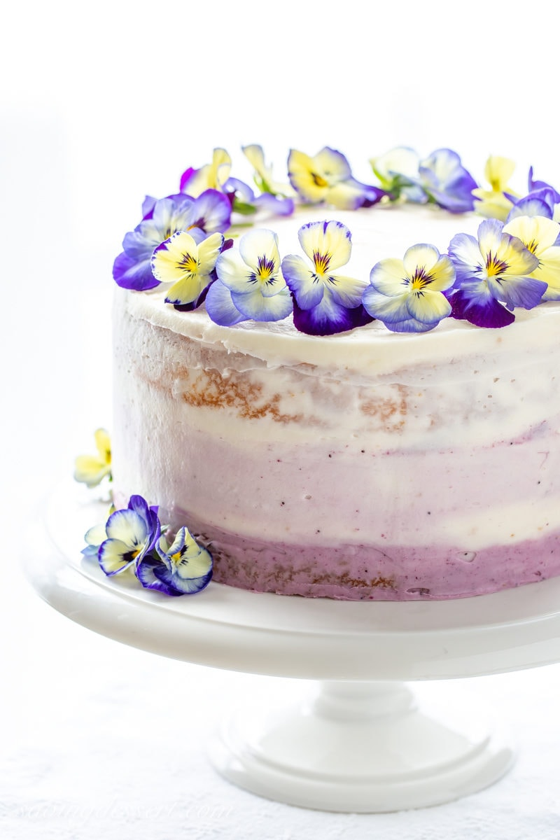 A three layer lemon cake with blueberry filling topped with edible blue and yellow pansies
