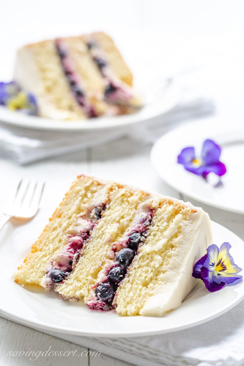 A slice of a three layer lemon cake with blueberry filling garnished with blue and yellow pansies