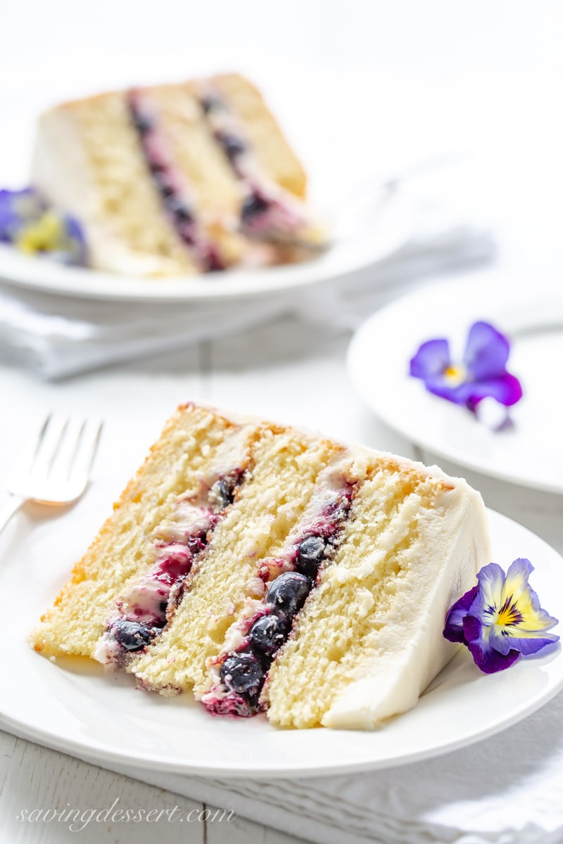A slice of a three layer lemon cake with a blueberry filling