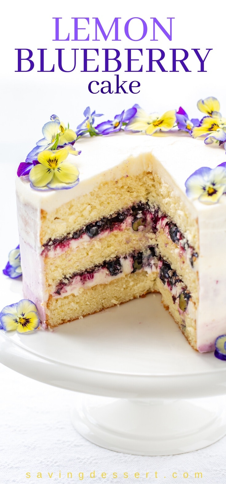 A sliced lemon blueberry cake topped with pansies for decoration