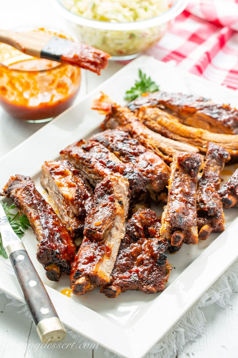 A large platter of barbecued pork ribs with barbecue sauce and cole slaw