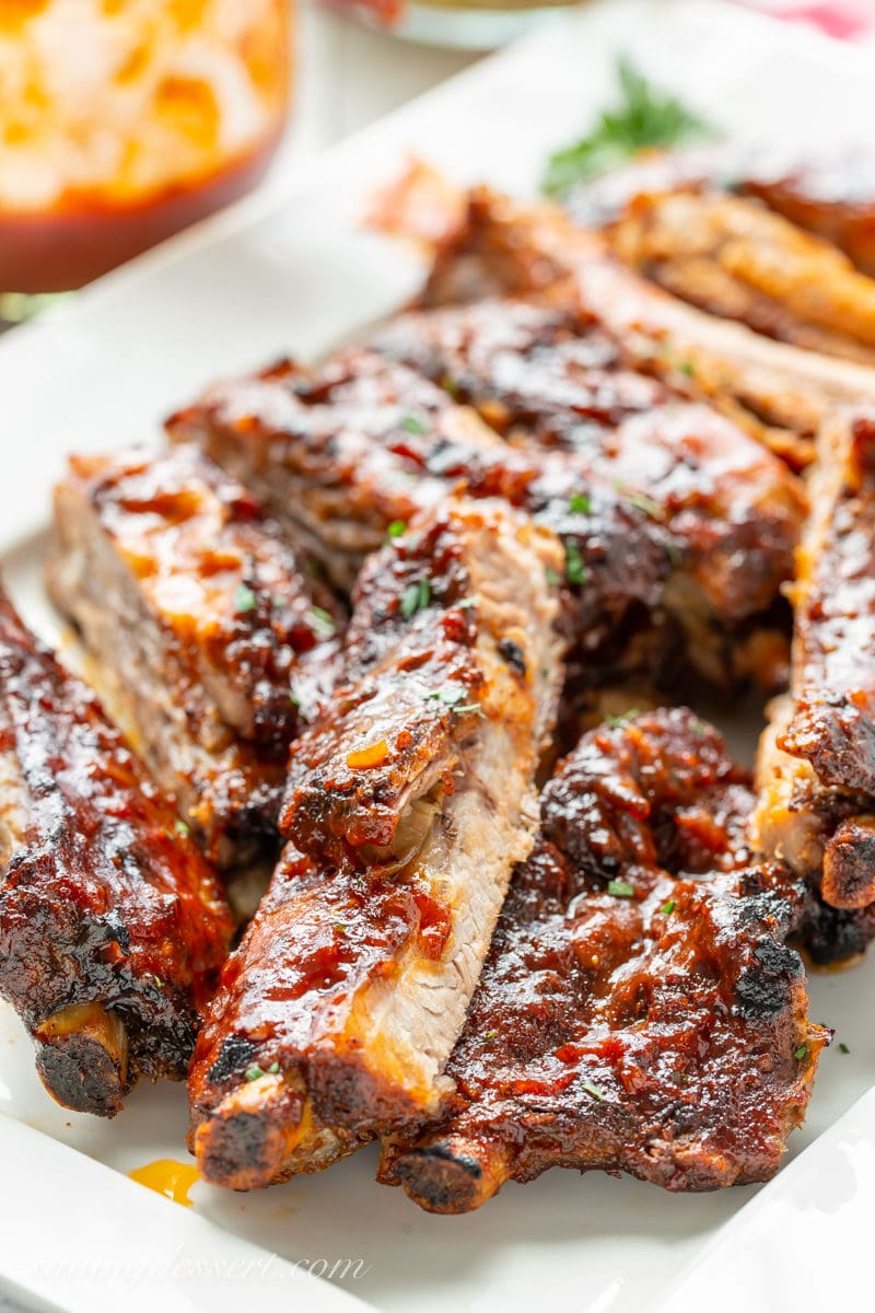 A platter filled with slow-cooker ribs slathered in homemade bbq sauce