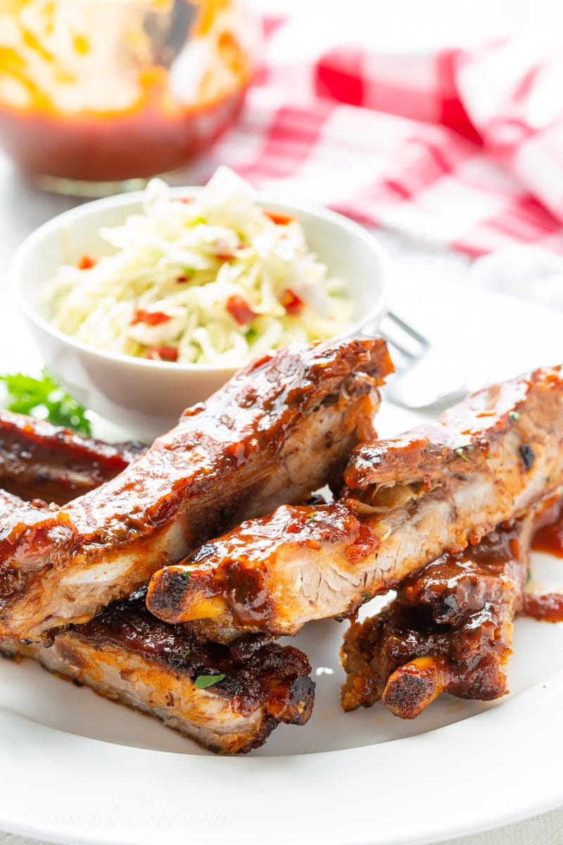 A plate with barbecued ribs with cole slaw and homemade sauce