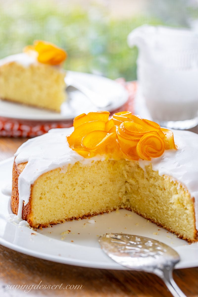 The inside of a Sunny Citrus Cake topped with icing and a group of candied orange slices