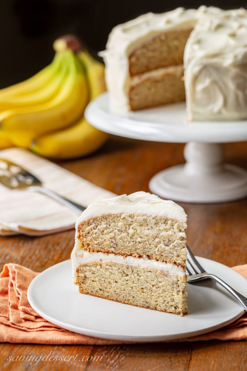 A slice of banana cake with bananas and the remainder of the cake in the background
