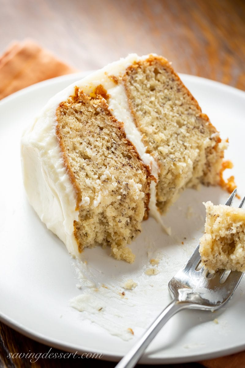 A close-up of a slice of banana cake with cream cheese frosting