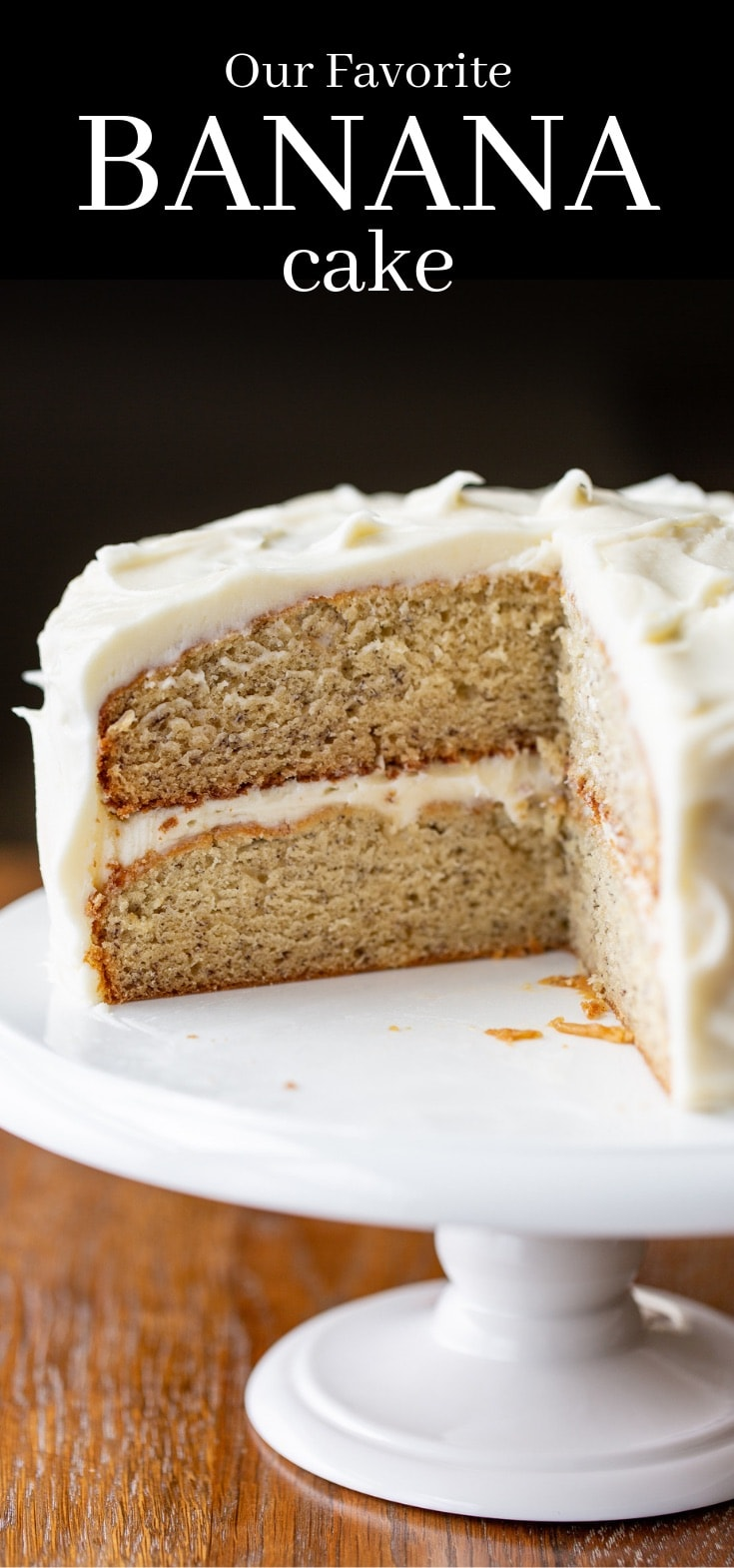 A two layer banana cake with cream cheese frosting sitting on a cake stand