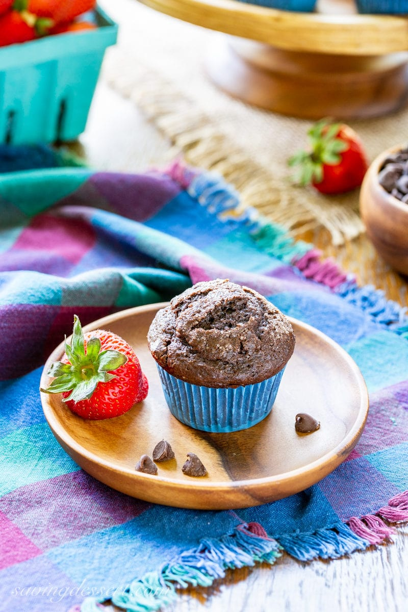 A dark chocolate muffin served with fresh strawberries
