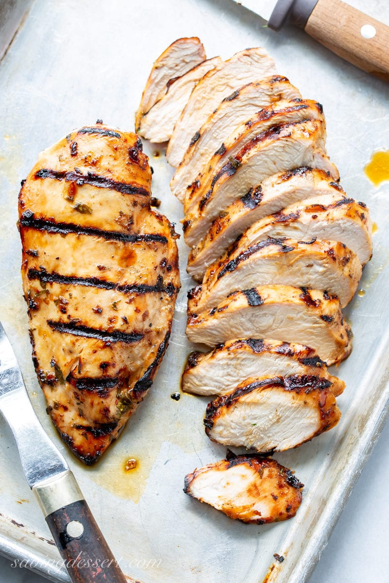 Sliced grilled chicken breasts on a tray
