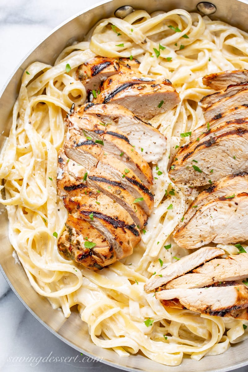Sliced grilled chicken breasts on a skillet of creamy fettuccine Alfredo with parsley