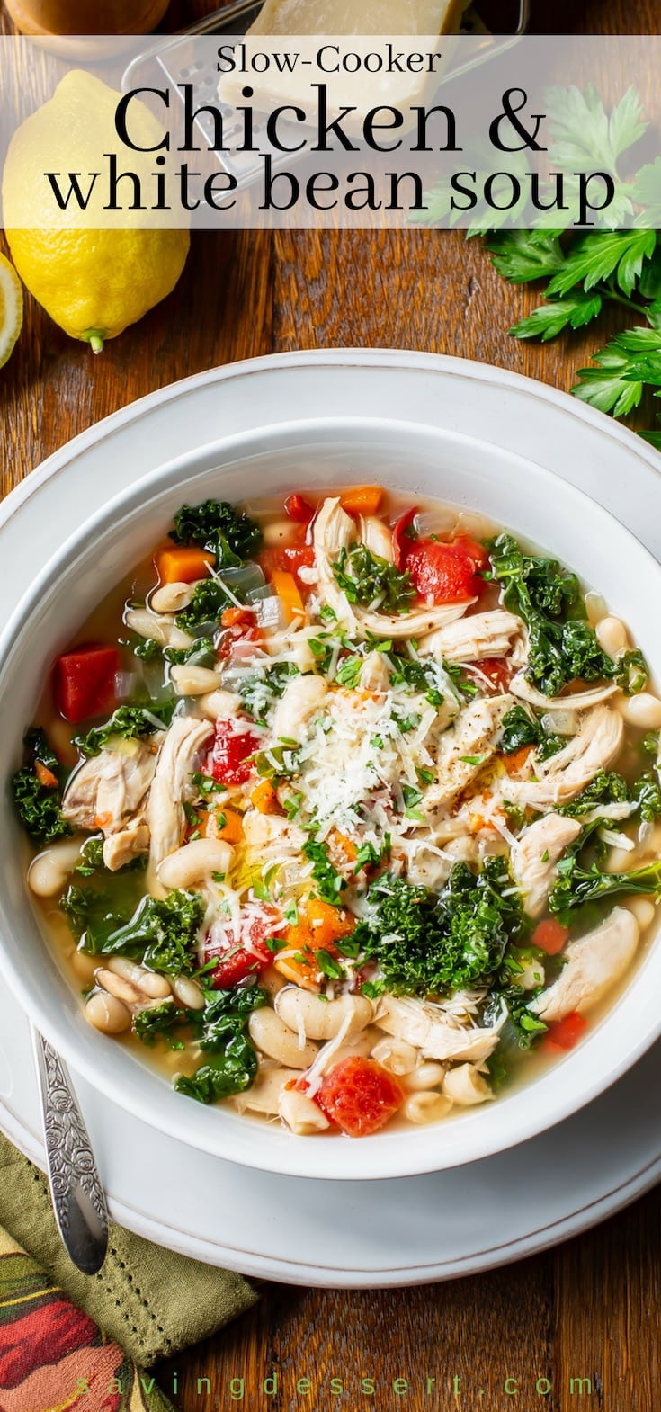 A bowl of healthy Chicken and White Bean Soup with kale, tomatoes and carrots