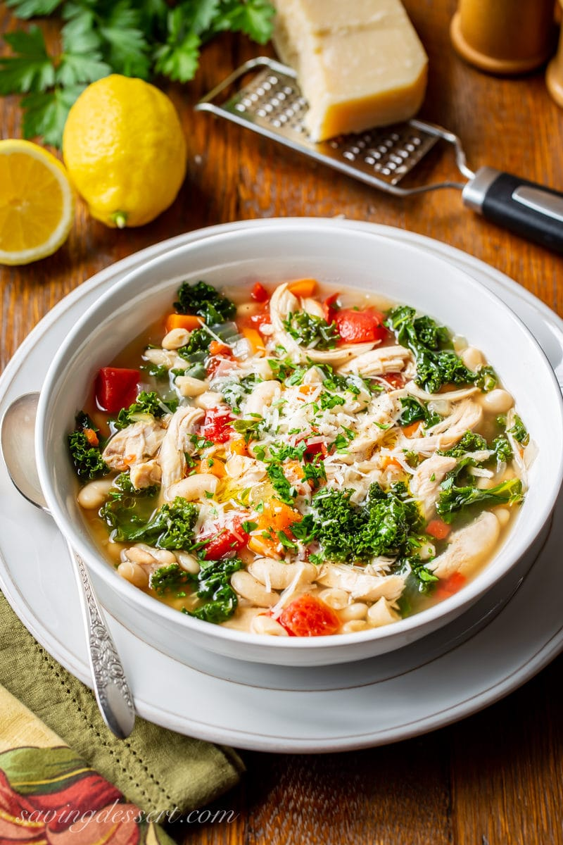 A bowl of Chicken & White Bean Soup with kale topped with fresh grated Parmesan and parsley