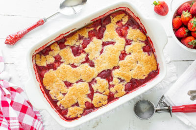 A casserole dish filled alongside a juicy strawberry cobbler alongside a crumbled biscuit topping Easy Strawberry Cobbler