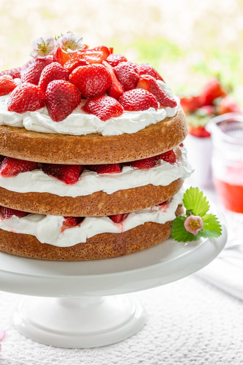 A big three layer strawberry shortcake cake with layers of whipped cream and red ripe strawberries