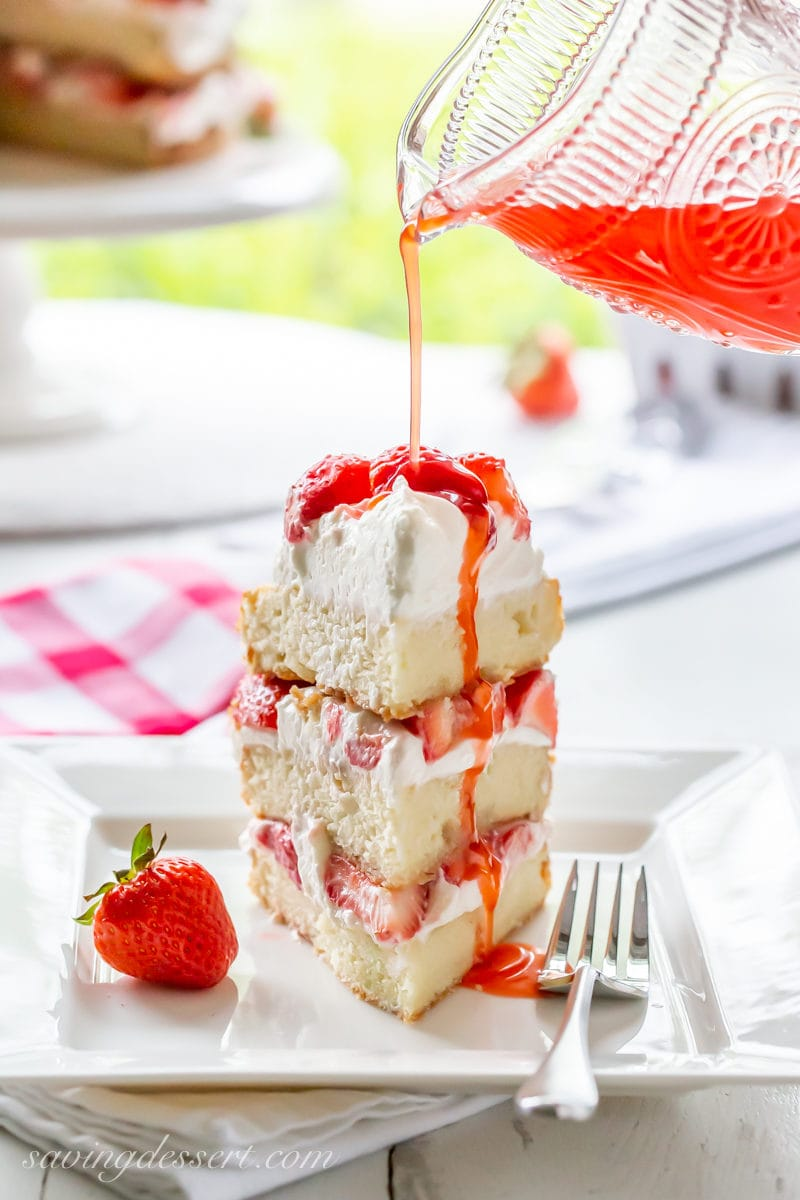 A slice of three layer strawberry shortcake cake drizzled with strawberry syrup