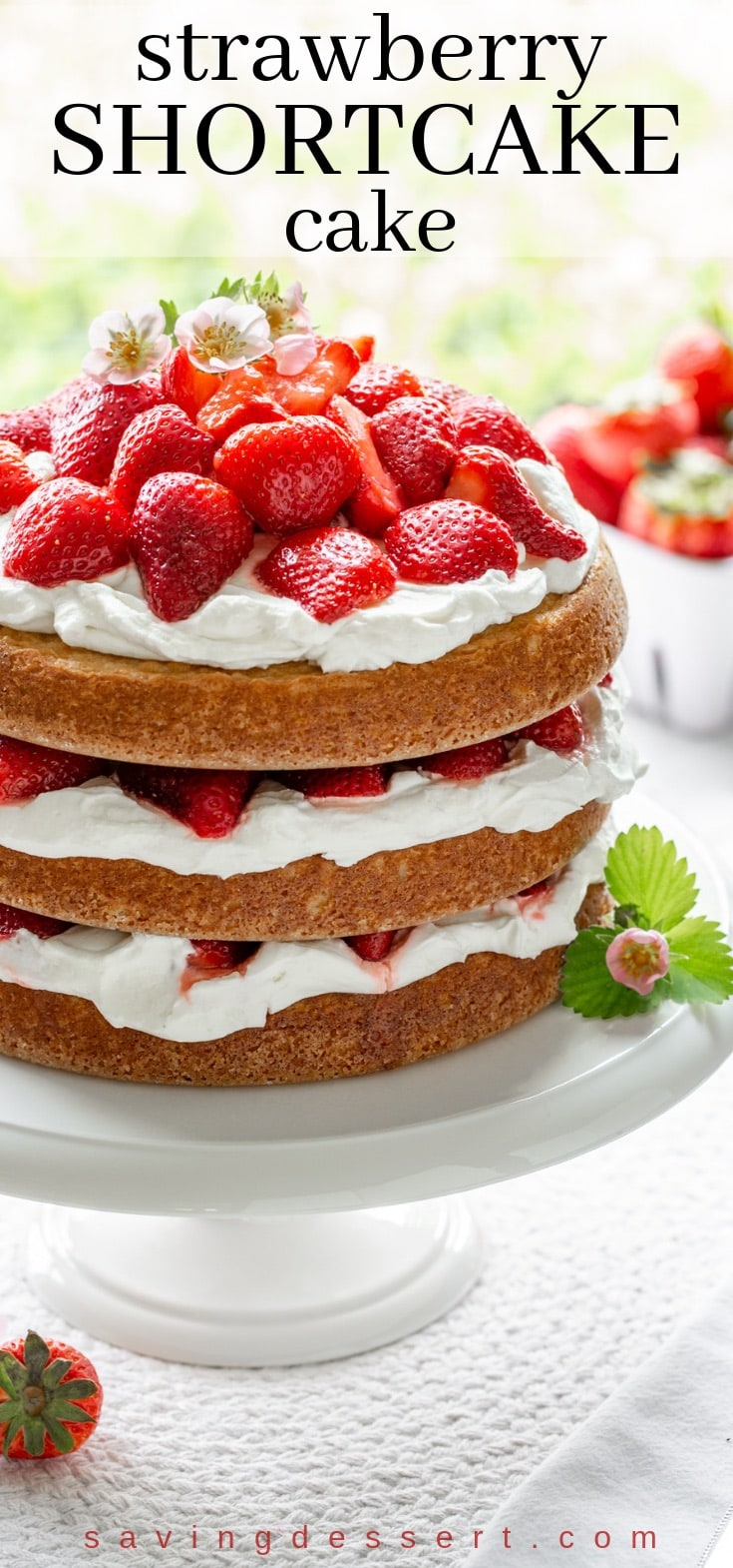 A three layer Strawberry Shortcake Cake piled high with fresh strawberries and topped with strawberry blossoms