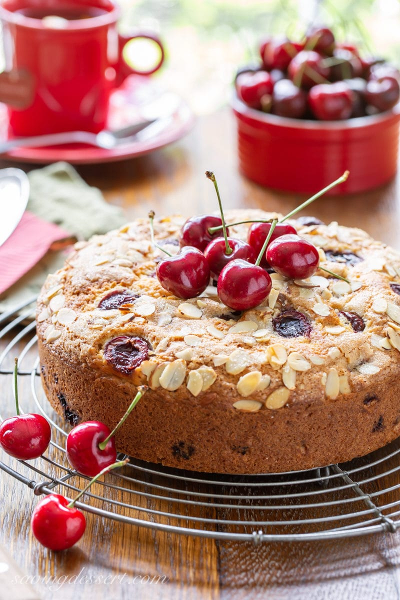 A single layer cherry breakfast cake on a rack with fresh cherries on top