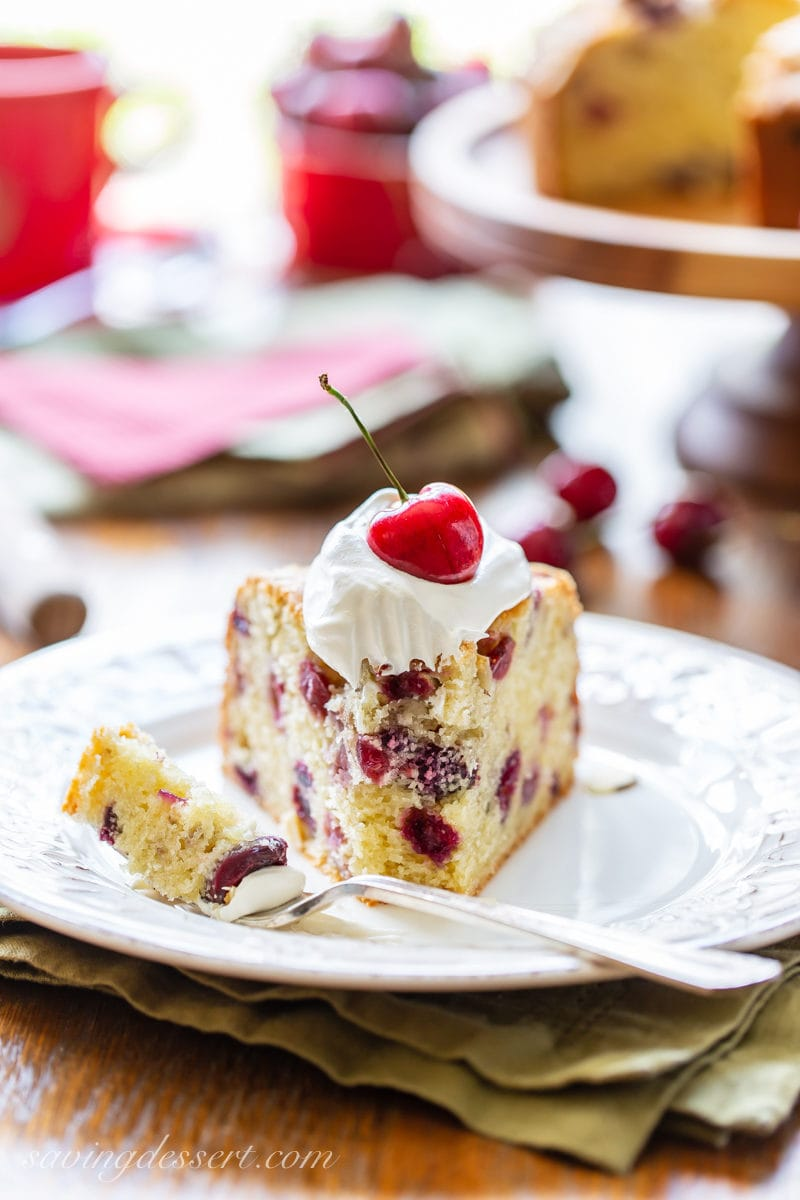 A slice of cherry almond breakfast cake with a dollop of whipped cream and a fresh cherry garnish