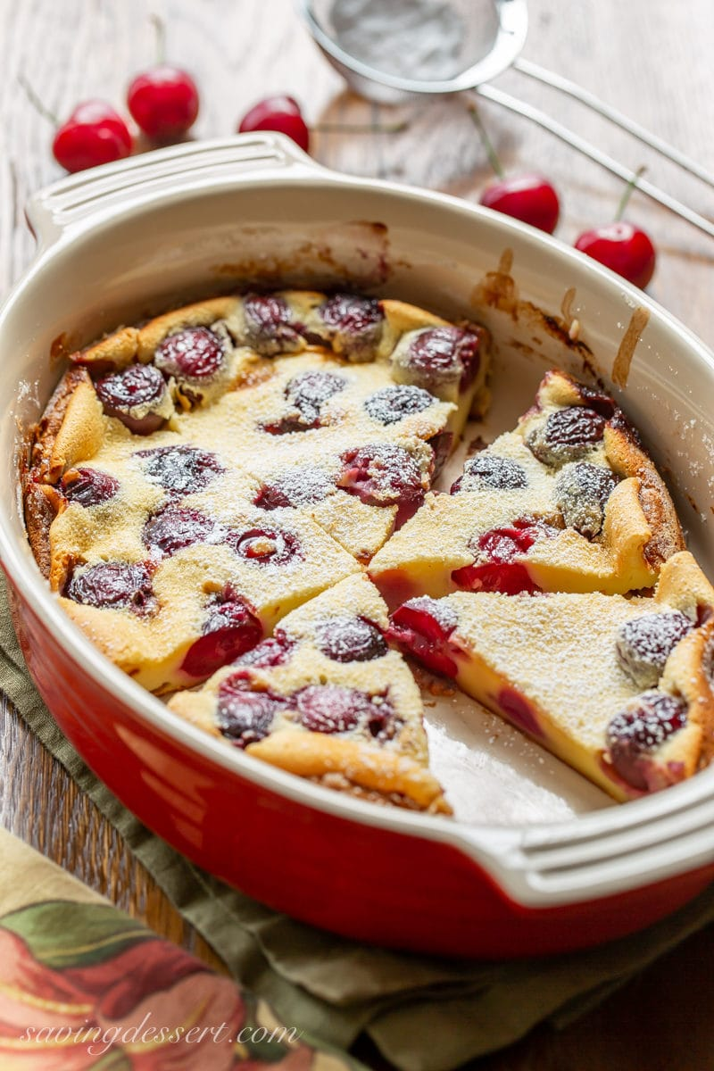 Casserole dish with sliced wedges of Cherry Clafoutis dusted with powdered sugar