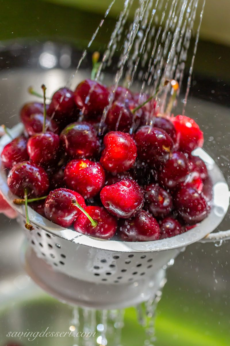 A bowl of fresh cherries washed in a cold stream of water