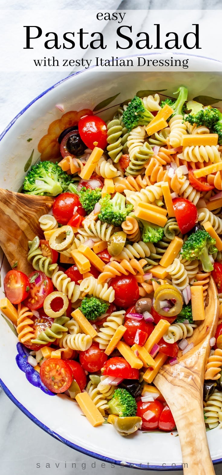 A large bowl of pasta salad with cheese, tomatoes and broccoli