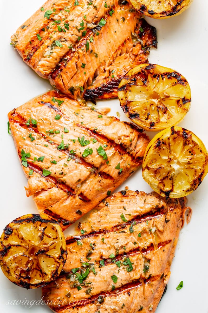 A platter of grilled salmon and lemons sprinkled with fresh herbs