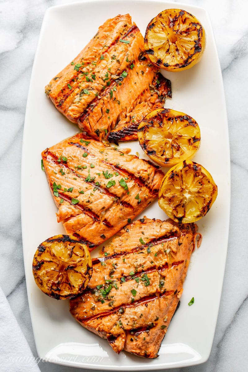 A platter with grilled salmon fillets and grilled lemons
