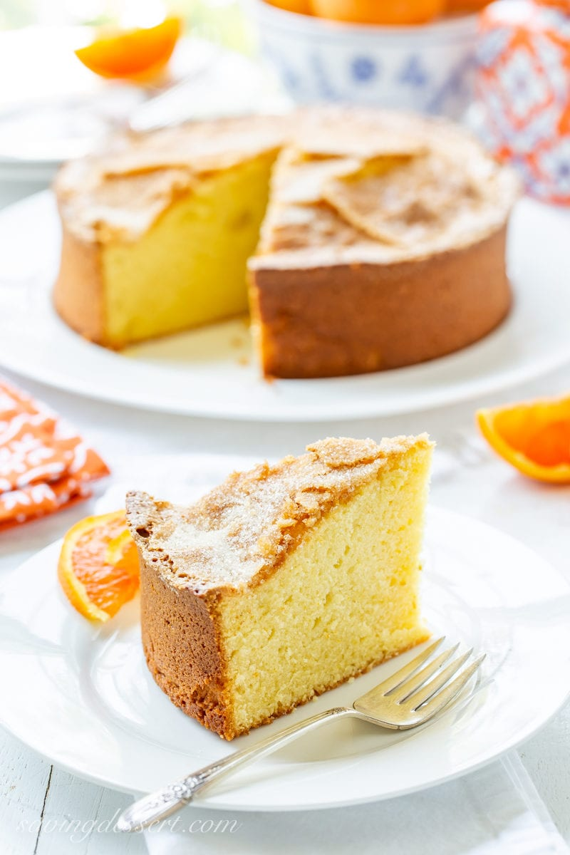 A big tall slice of Orange Olive Oil Cake with sliced Cara Cara oranges