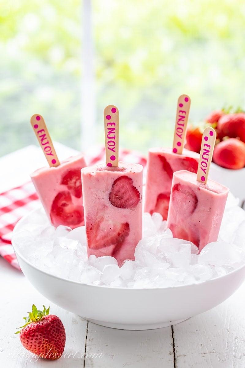A bowl of fresh strawberry yogurt popsicles