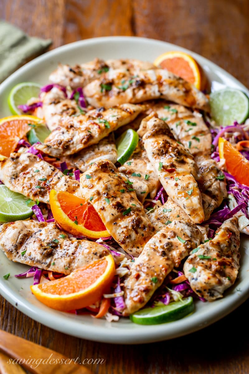 A platter of grilled chicken tenders with a light chipotle sauce served over purple slaw with orange and lime wedges