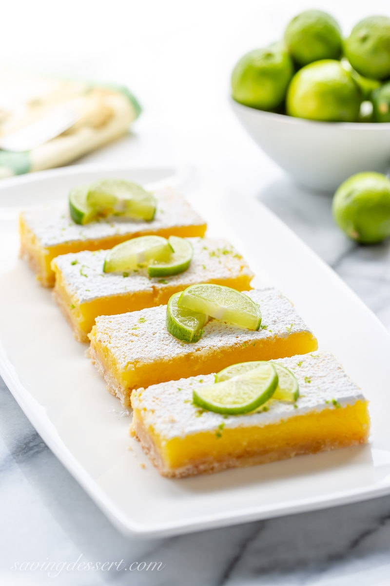 A plate of key lime bars garnished with powdered sugar and key lime wedges