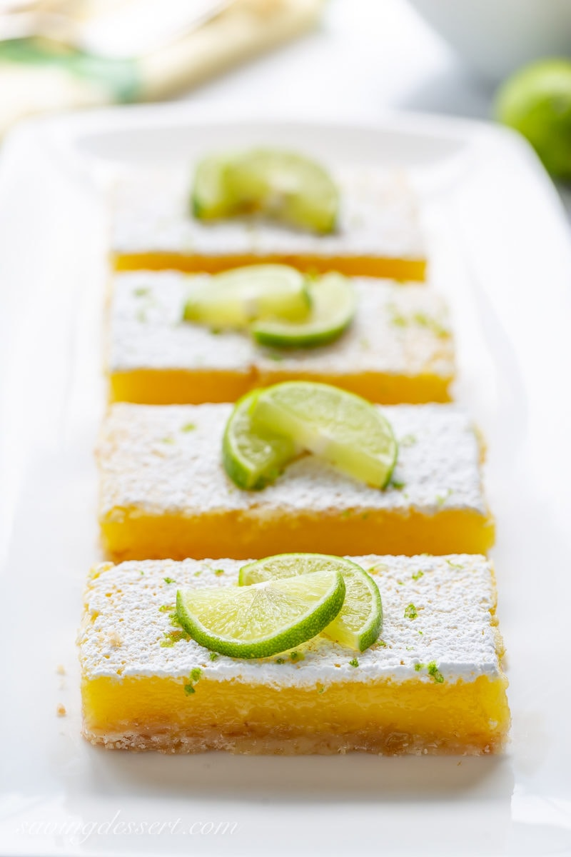 Coconut Key Lime Bars on a plate garnished with key limes and powdered sugar