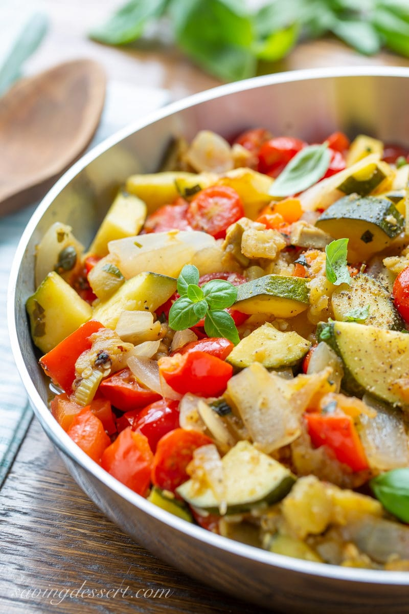 A skillet filled with eggplant caponata with zucchini, tomatoes, onions and fresh basil