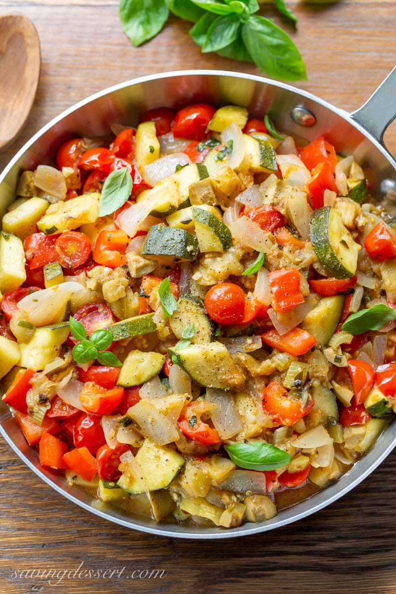A skillet filled with eggplant caponata with zucchini, onions, tomatoes and red bell pepper