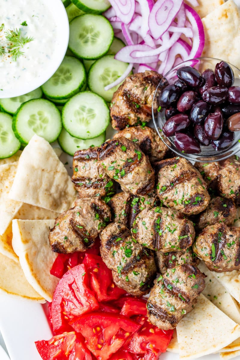 A platter of kebabs, olives, tomato, cucumber-yogurt sauce, onion and pita wedges