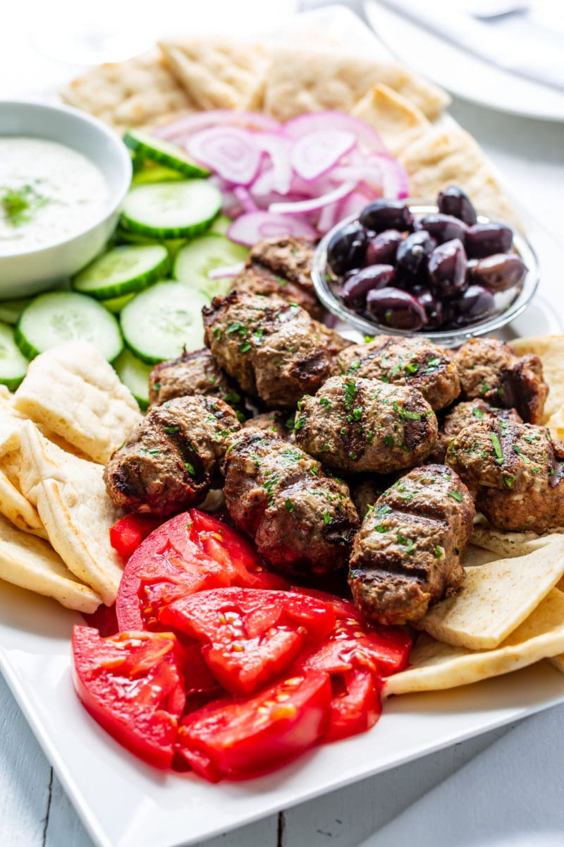 Grilled Kebabs on a platter with olives, tomatoes, pita, cucumbers and onions