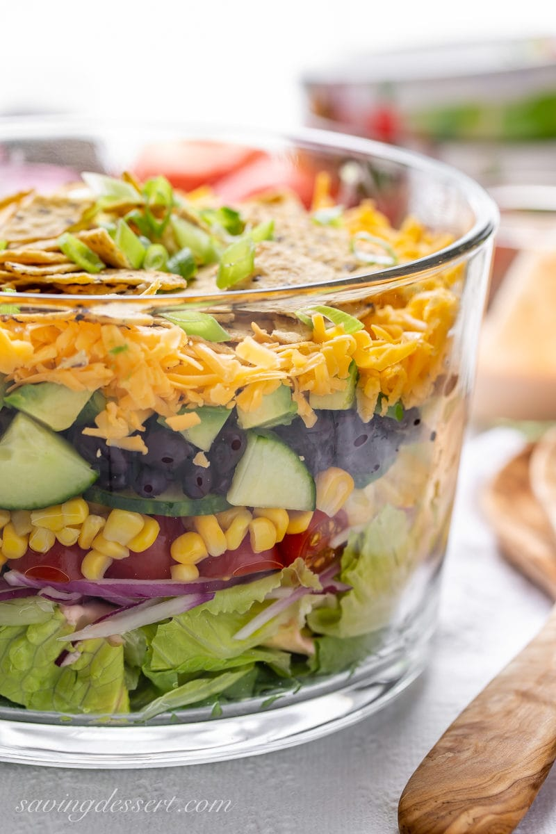 A clear glass trifle bowl with a layered Mexican Salad with corn, beans, cheese and chips on top