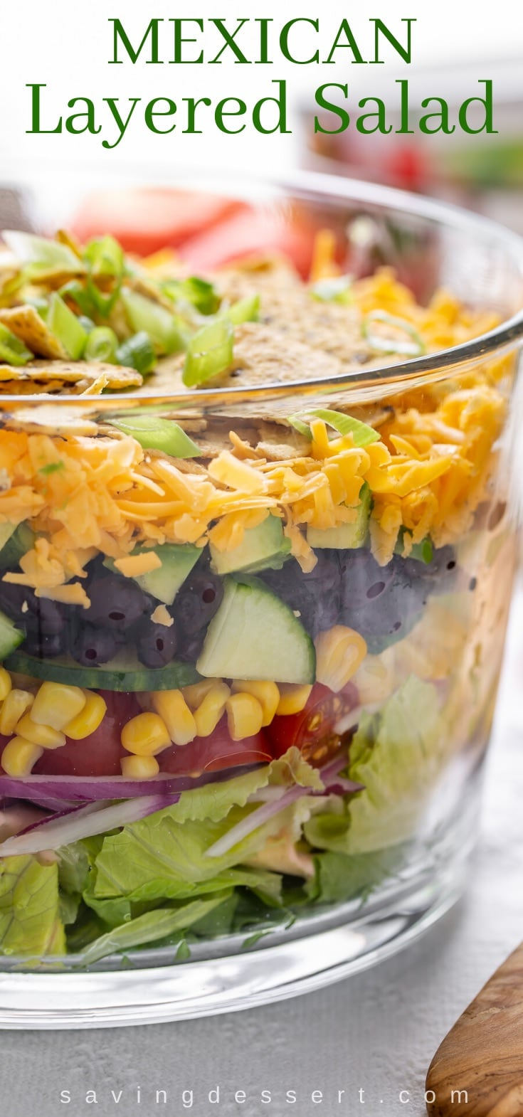 A trifle bowl filled with Mexican Layered Salad with chips on top
