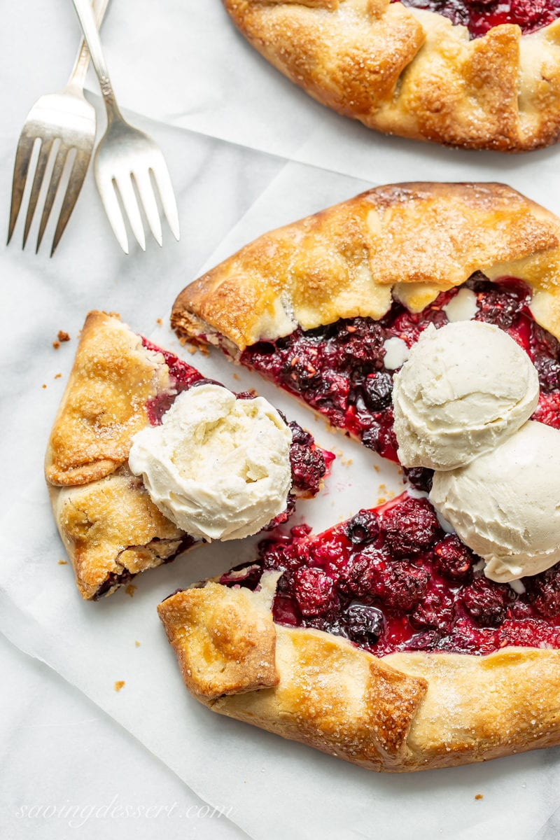 A sliced mixed berry crostata topped with scoops of vanilla bean ice cream